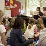 Учителка чете на деца в училище